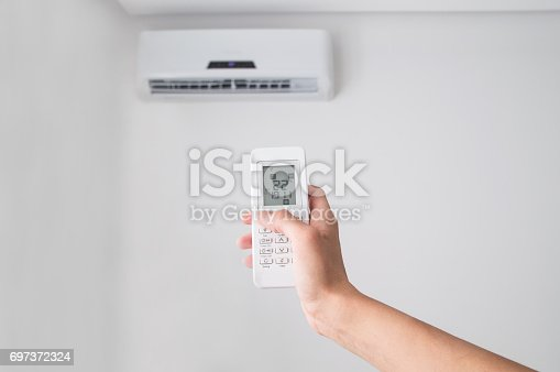 istock Hand holding remote control for air conditioner on white wall. 697372324