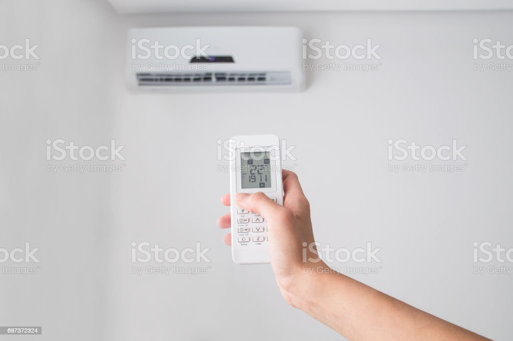 Hand holding remote control for air conditioner on white wall. stock photo