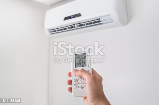 istock Hand holding remote control for air conditioner on white wall. 811483106