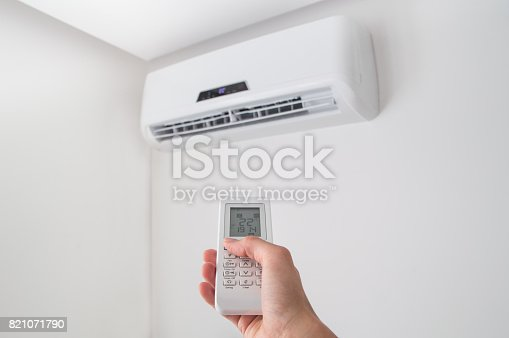 istock Hand holding remote control for air conditioner on white wall. 821071790