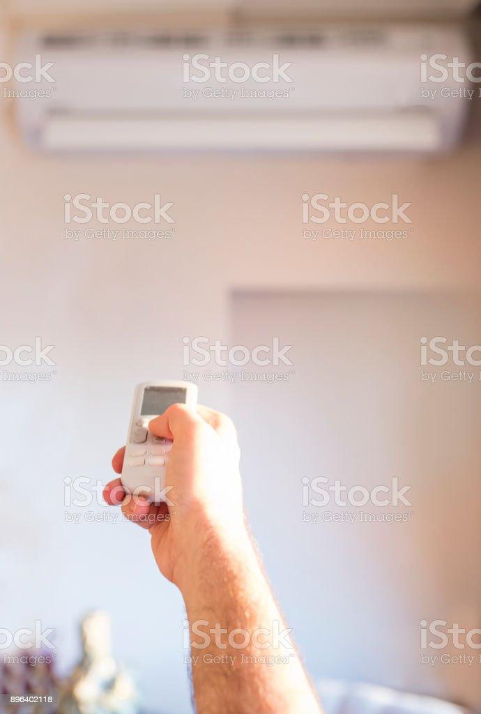 Mano que sostiene el control remoto para aire acondicionado en pared blanca - foto de stock
