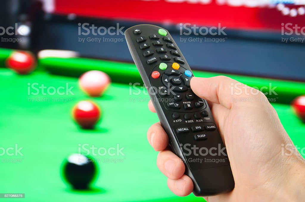Hand holding remote control in front of tv stock photo