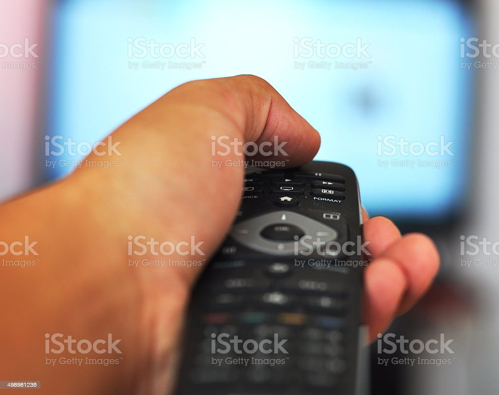 Hand holding remote controller with tv in the background stock photo
