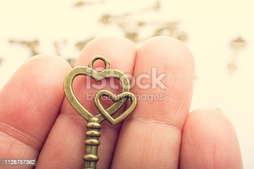Hand and retro style metal keys on a white background