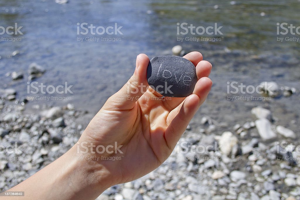 "hand holding rock with ""love ""written on it royalty-free stock photo"