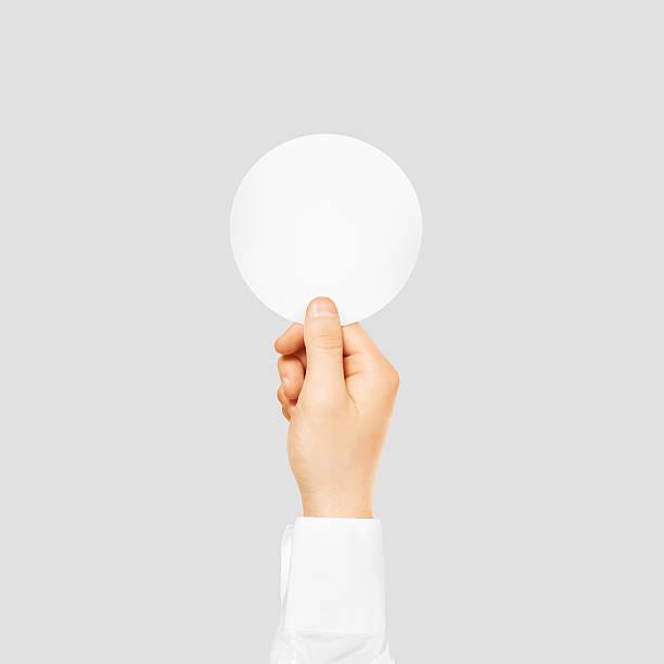 hand holding round blank white sticker mock up isolated on - flyer inspiration stock-fotos und bilder