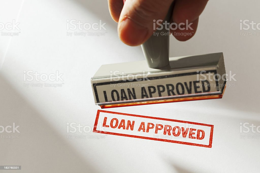"""Hand Holding Rubber Stamp Stamping Red """"LOAN APPROVED"""" on Paper stock photo"""