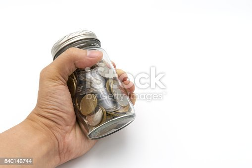 Hand holding saving money concept of collecting coins (Thai money) in a glass bottle on isolate white background.