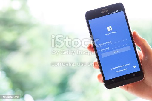 istock hand holding screen shot of Facebook application 588359078