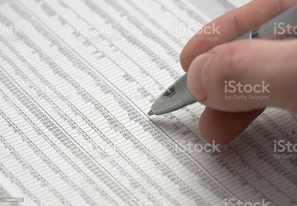 Hand holding shiny pen over spreadsheet royalty-free stock photo