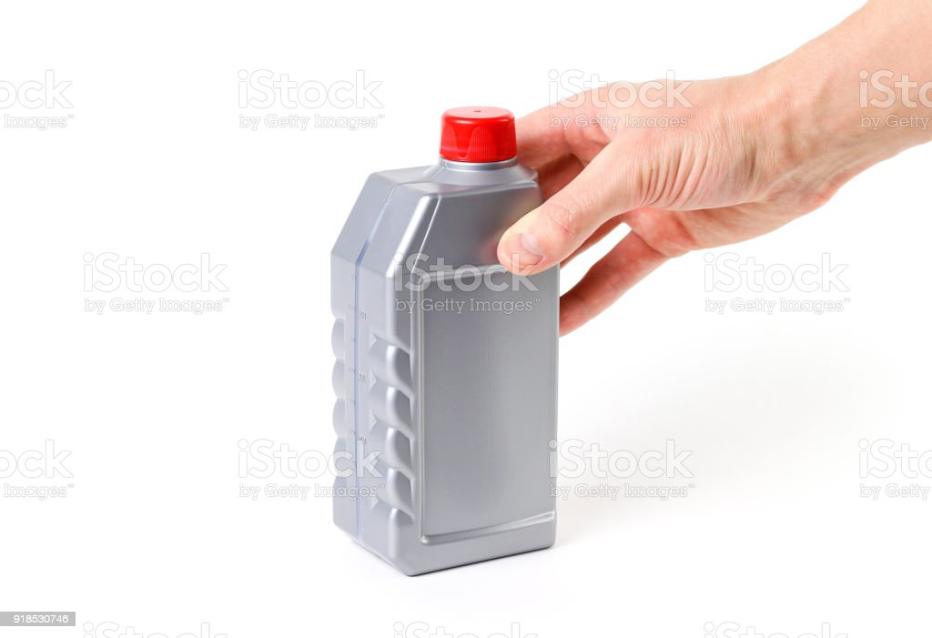 Hand holding silvery measuring bottle with red lid. Brake fluid stock photo