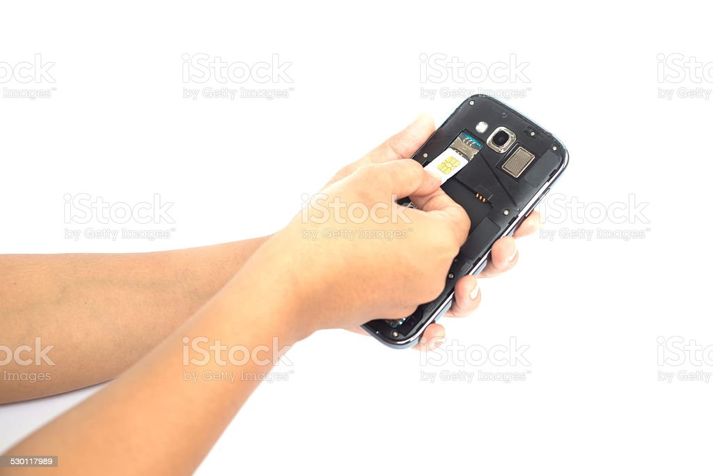 Hand holding sim card and put into smartphone stock photo