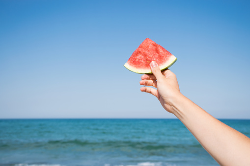 Hand holding slice of watermelon on the beach. Summertime, watermelon lover, summer sale concept