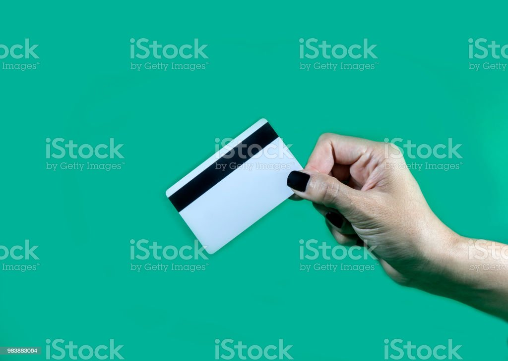 Hand holding smart card on a green background.