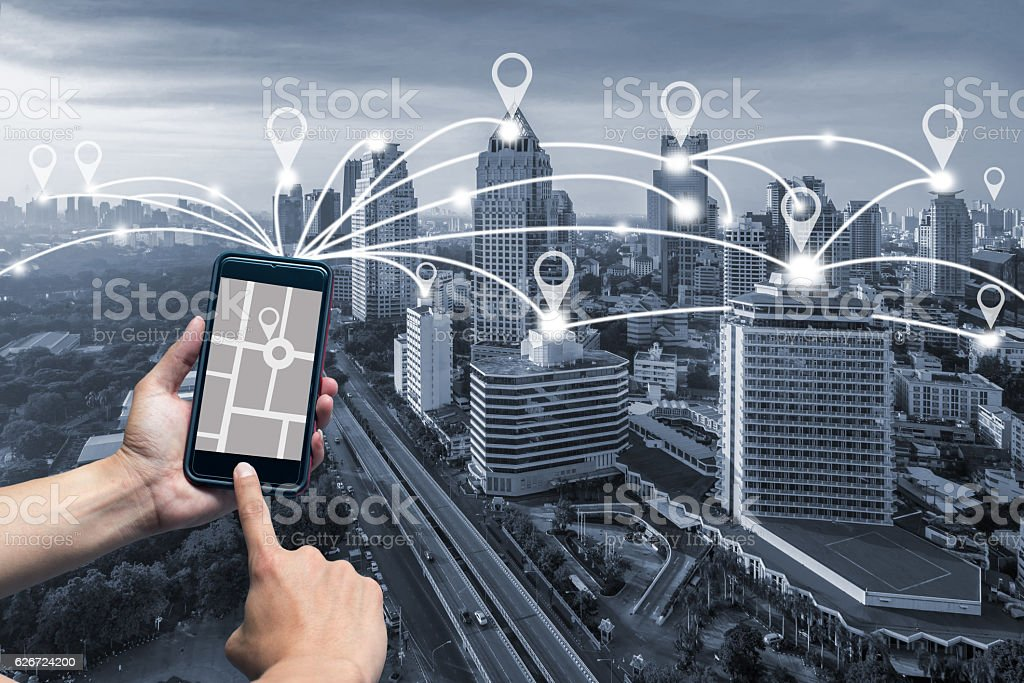 hand holding smart phone and cityscape with Map pin flat stock photo
