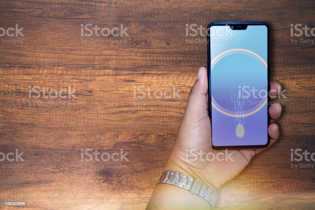 hand holding smart phone and finger scan to log in device stock photo
