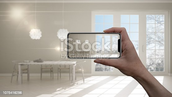 istock Hand holding smart phone, AR application, simulate furniture and interior design products in real home, architect designer concept, blur background, classic kitchen with beige details 1075416256