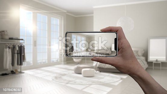 istock Hand holding smart phone, AR application, simulate furniture and interior design products in real home, architect designer concept, blur background, classic bedroom 1075428232