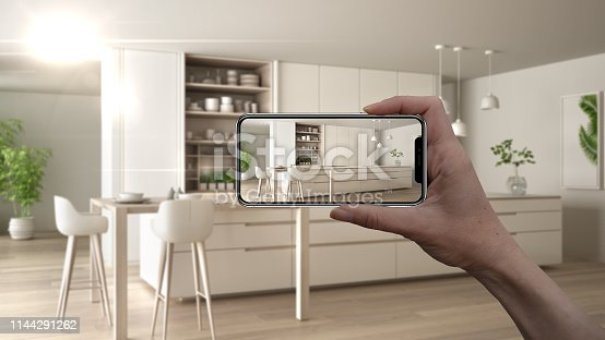 istock Hand holding smart phone, AR application, simulate furniture and interior design products in real home, architect designer concept, blur background, modern white and wooden kitchen 1144291262
