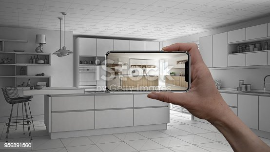 istock Hand holding smart phone, AR application, simulate furniture and interior design products in real home, architect designer concept, sketch project background, modern kitchen 956891560