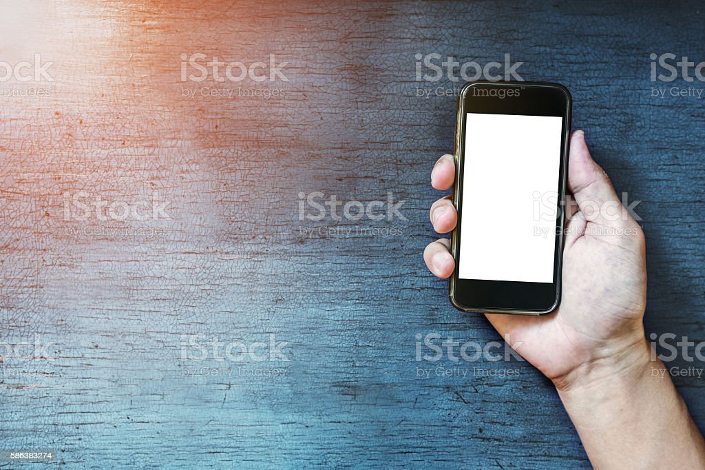 Hand holding smart phone on old blue wooden desk stock photo