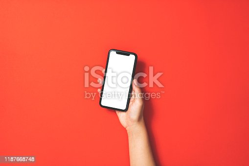 istock Hand holding smart phone on red background 1187668748