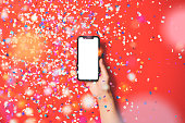 Hand holding smart phone on red background under confetti rain