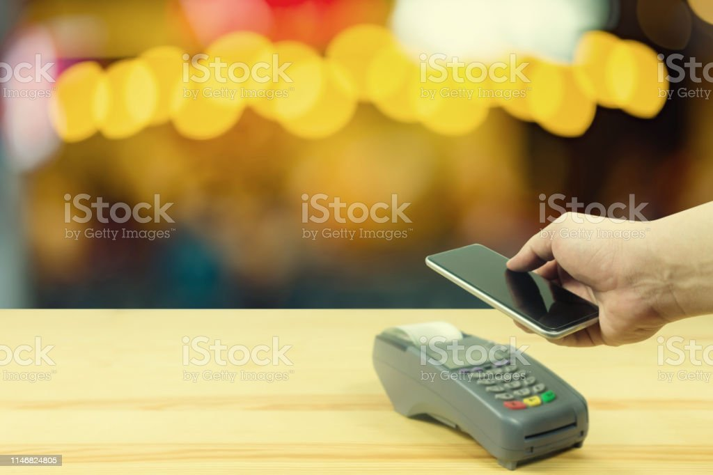 Hand holding smart phone over credit card machine with supermarket...