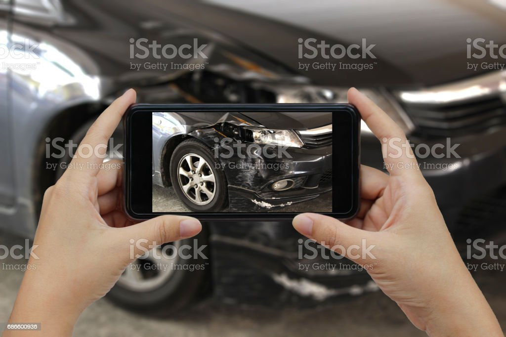 Hand holding smart phone take a photo at The scene of a car crash, car accident for insurance stock photo