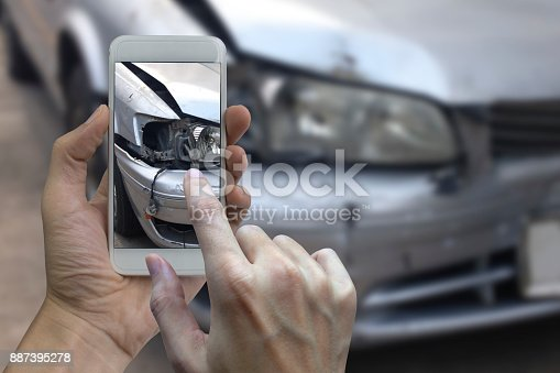 istock Hand holding smart phone take a photo at The scene of a car crash, car accident for insurance 887395278