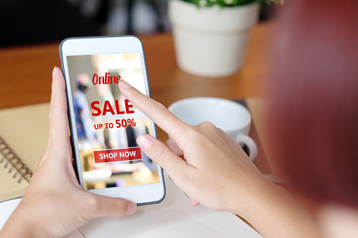 istock Hand holding smart phone with black friday sale on screen device over blur store background, business and technology, online shopping, digital marketing concept 1001327622