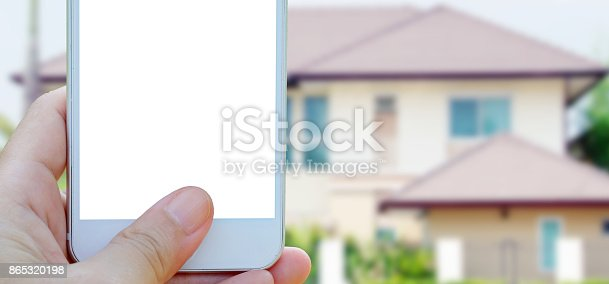 istock Hand holding smart phone with blank on screen over blurred house background with copy space, smart home concept template 865320198