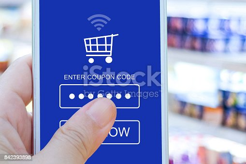 istock Hand holding smart phone with discount coupon code on screen over blur supermarket background, on line shopping ,business, E-commerce, technology and digital marketing background 842393898