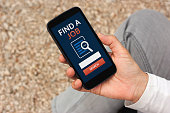 istock Hand holding smart phone with find a job concept on screen 687023672