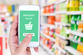 istock Hand holding smart phone with grocery shopping online on screen over blur supermarket background, retail business and technology concept 665045554