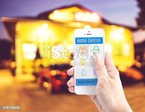 istock Hand holding smart phone with home control application 478729430