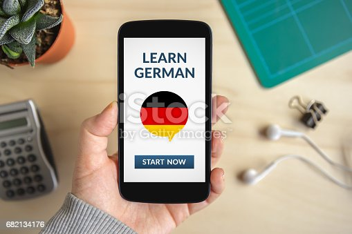 istock Hand holding smart phone with learn german concept on screen 682134176