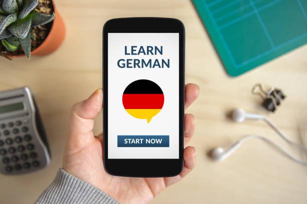 hand mit smartphone mit lernen deutsche konzept auf dem bildschirm - studieren in deutschland stock-fotos und bilder