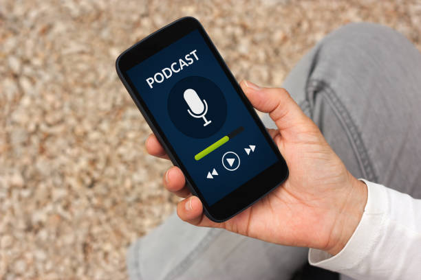 Hand holding smart phone with podcast concept on screen stock photo