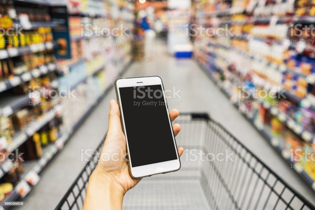 Hand mit Smartphone mit Schubkarre im Supermarkt – Foto