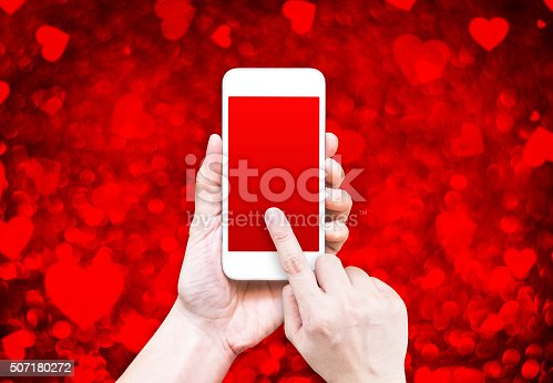 istock Hand holding smart phone with red screen on red heart 507180272