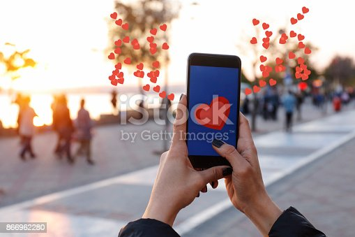 istock Hand holding smart phone with sending heart 866962280