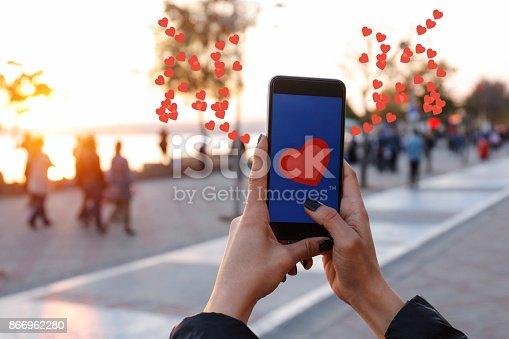 898149690 istock photo Hand holding smart phone with sending heart 866962280