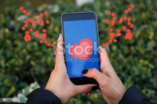 898149690 istock photo Hand holding smart phone with sending heart 867729702