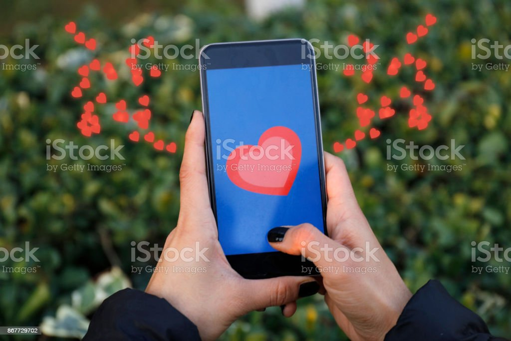 Hand holding smart phone with sending heart stock photo