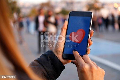 898149690 istock photo Hand holding smart phone with sending heart 867746454
