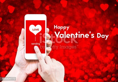 istock Hand holding smart phone with sending love word and heart 505304772