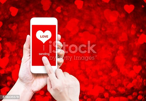 istock Hand holding smart phone with sending love word and heart 516005378