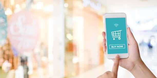 hand holding smart phone with shopping online device on screen over blue background with copy space, business and technology, online shopping concept - online shopping imagens e fotografias de stock