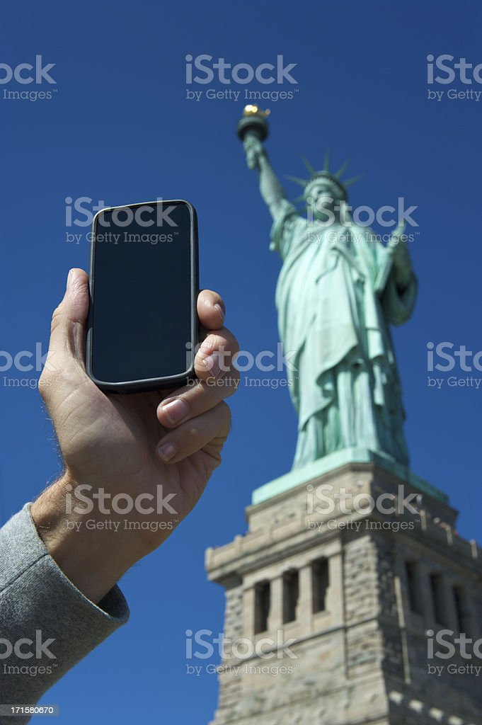 Hand Holding Smartphone at Statue of Liberty royalty-free stock photo